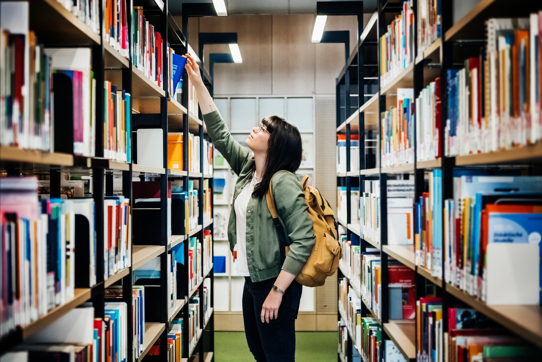 Student reaching for a book in the university library