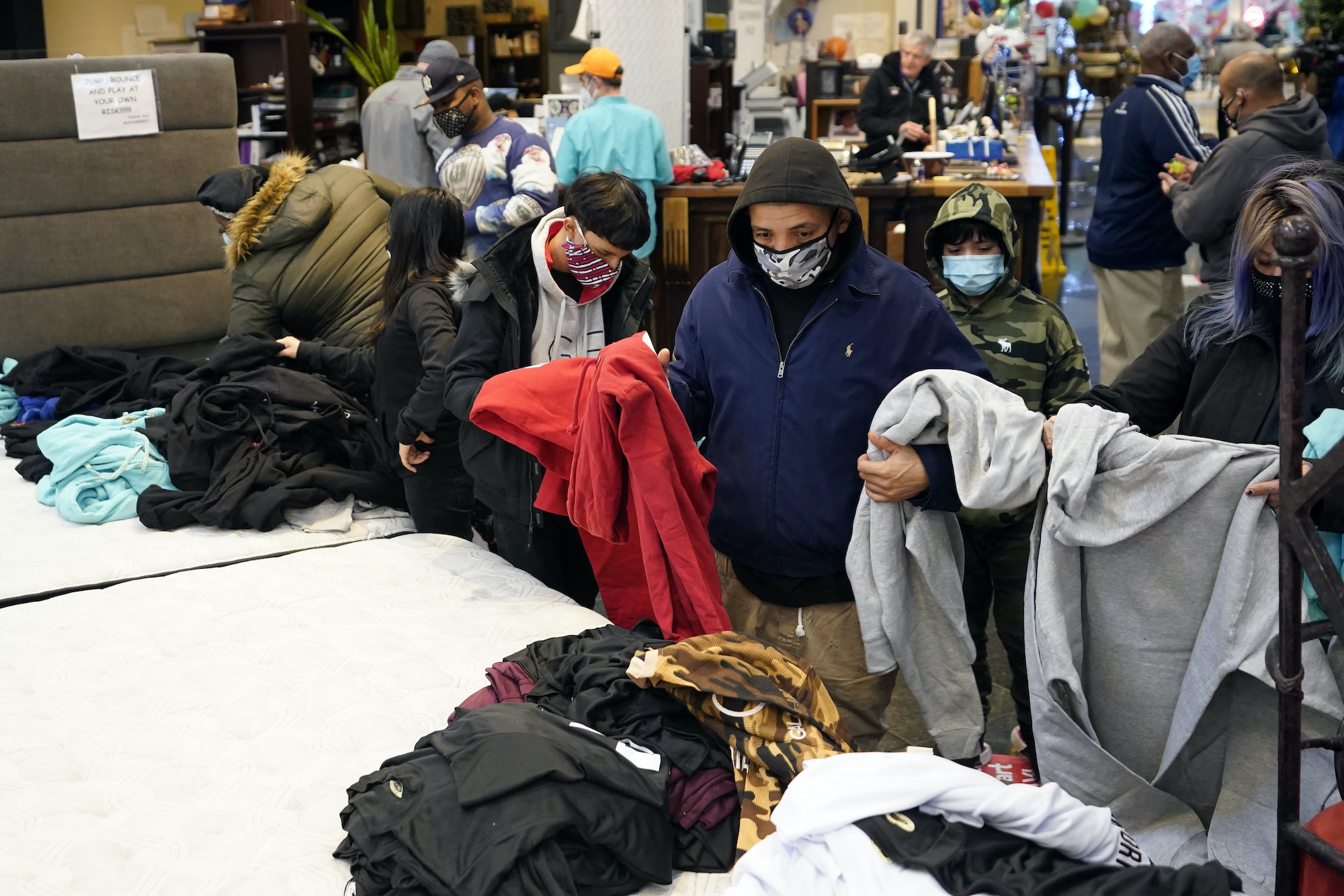 A person wearing a hoodie holds sweatshirts and looks through piles of clothing inside a furniture store