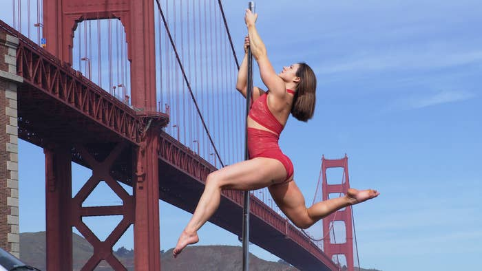 A woman poses on a pole with the Golden Gate Bridge in the background.