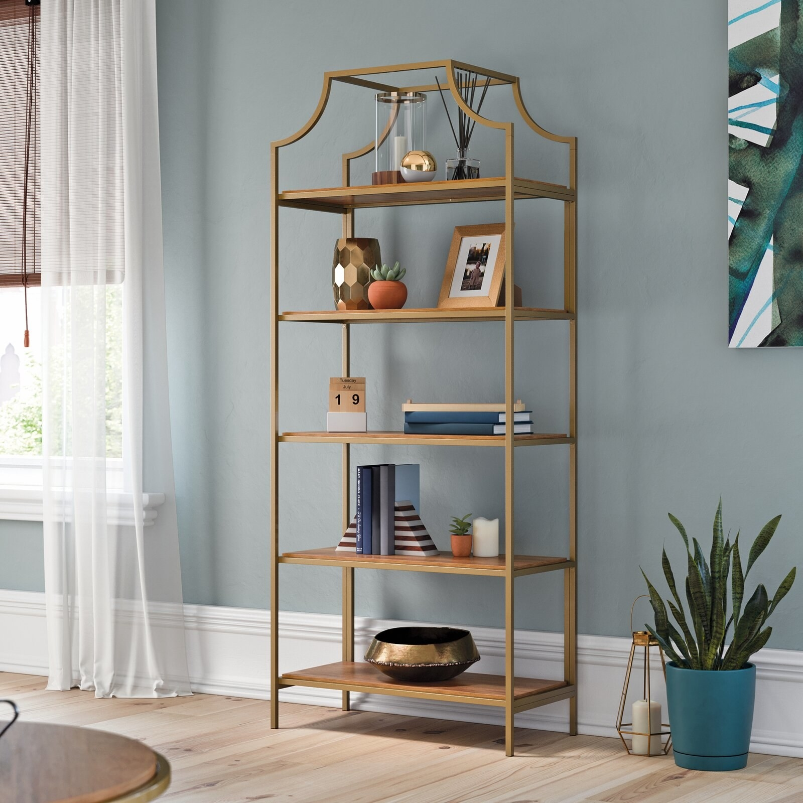 The bookshelf, which has five wooden shelves on an open metal frame, with an arched crown flourish on top