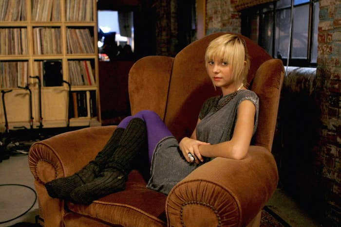 Taylor Momsen sits on a chair in an episode of Gossip Girl wearing a dress, tights, and knee-high socks