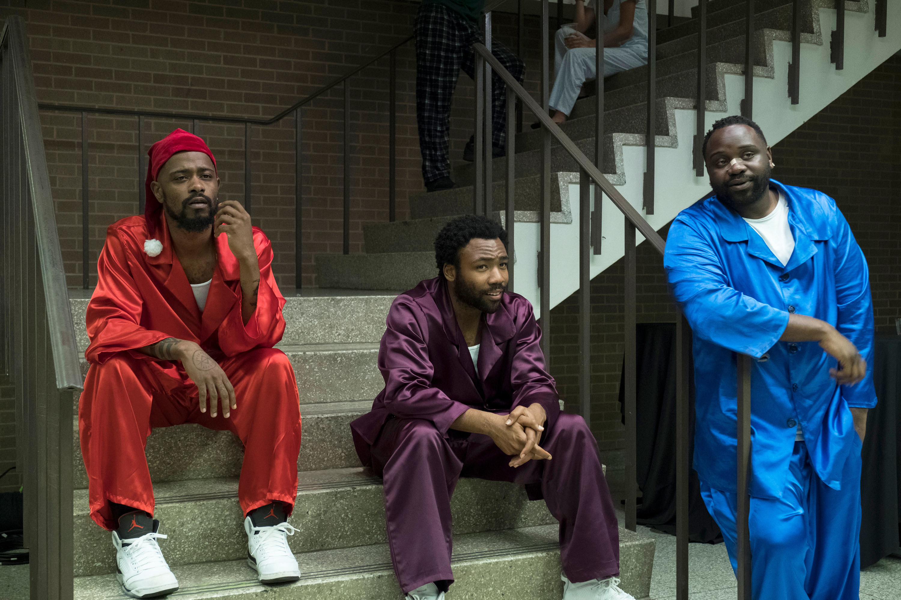 Lakeith Stanfield, Donald Glover, and Brian Tyree Henry sitting on steps in coordinating pajamas in the TV show Atlanta