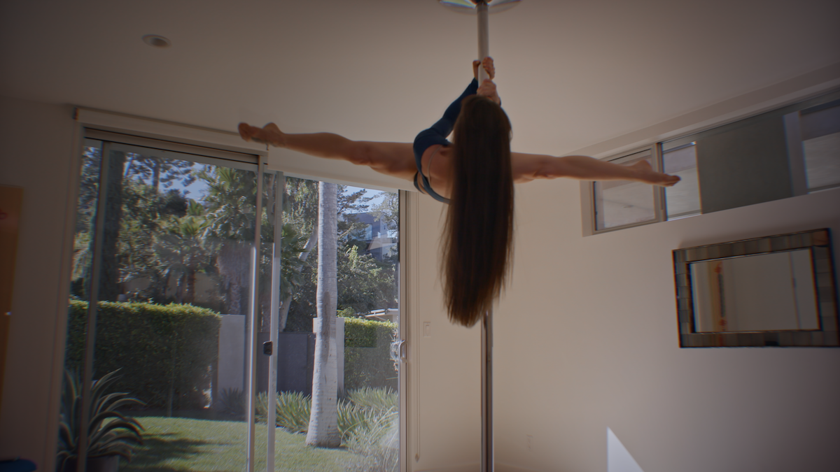 A woman does splits while high up on a pole