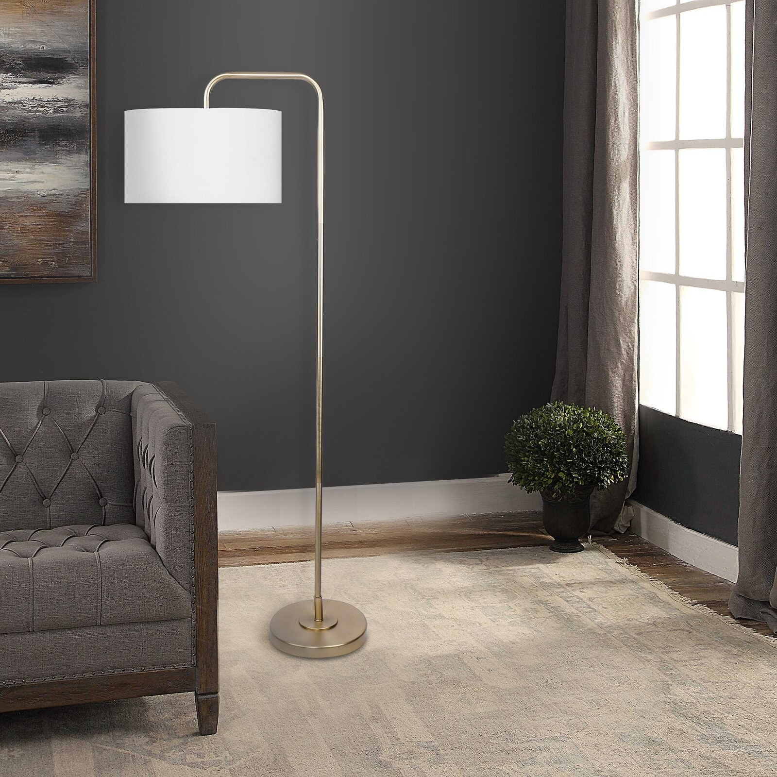 The lamp, which has an arched, curved neck, with a drum shade and bulb hanging from the end