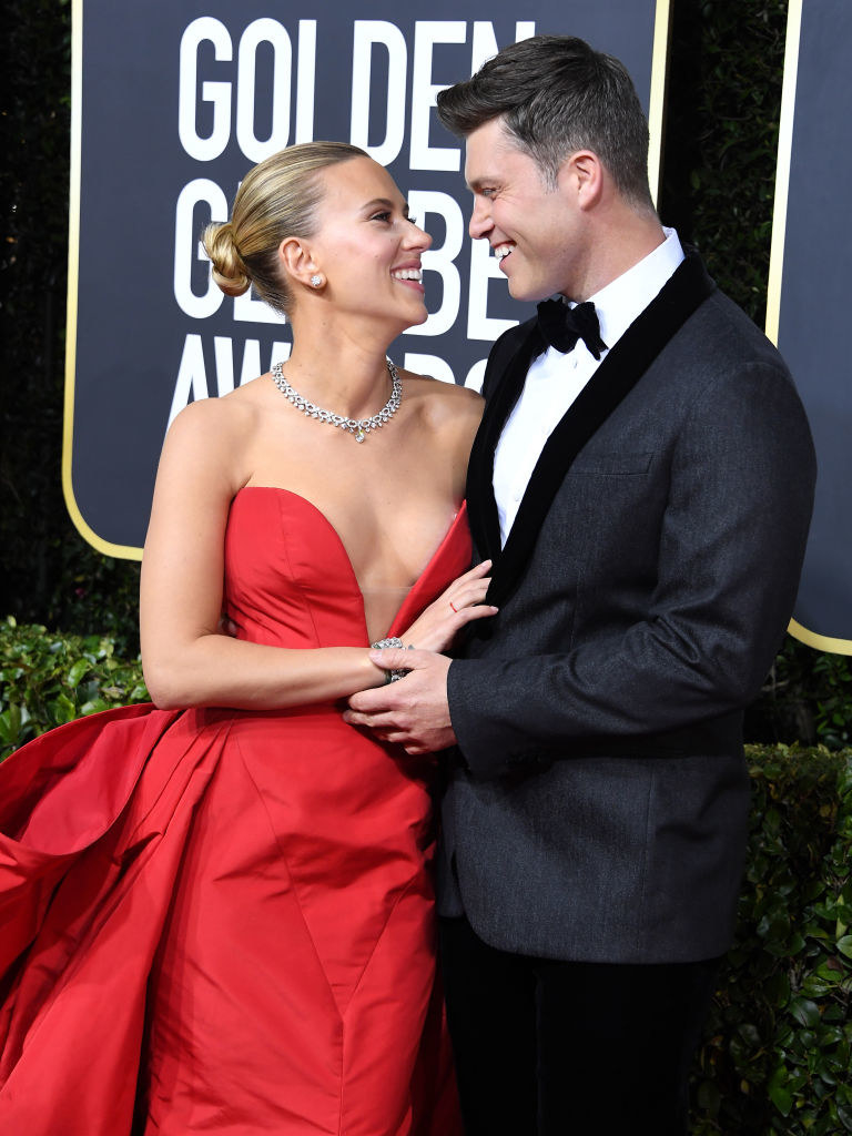 Scarlett Johansson, wearing a sweetheart, strapless dress with a large train, looks up at Colin Jost, who's wearing a tux, at the 77th Annual Golden Globe Awards