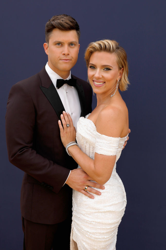 Colin Jost with his arms around Scarlett Johansson, who's wearing an off-the-shoulder sequined dress, at the 70th Annual Primetime Emmy Awards