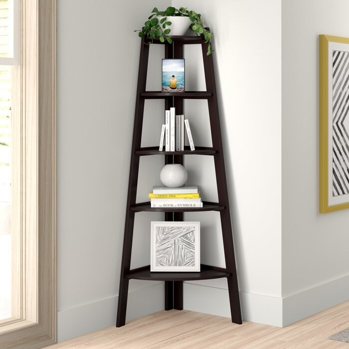 The bookcase, which fits in a corner and has three legs, with five shelves which start large at the bottom of the bookcase, and end up small at the top