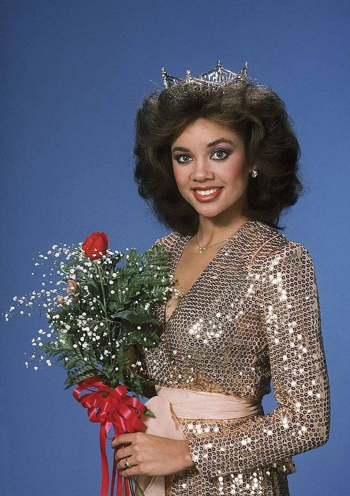 Vannessa Williams in 1983 at the Miss America Pageant wearing her tiara and a sequined dress with a sash belt while holding a rose