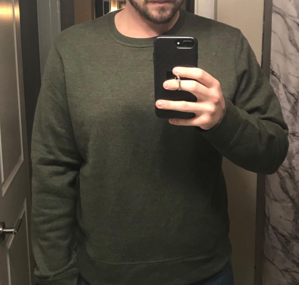 A reviewer wearing the crewneck in green