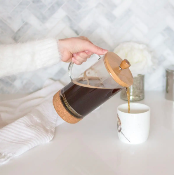Someone pouring a cup of coffee out of the bamboo-lidded French press
