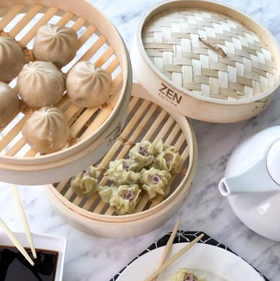 A set of steaming baskets containing dim sum dumplings