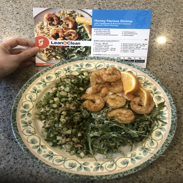 TheNews.Top editor Elizabeth Lilly holds a Gobble Honey-Harissa Shrimp recipe card above a plate filled with golden-cooked shrimp and greens