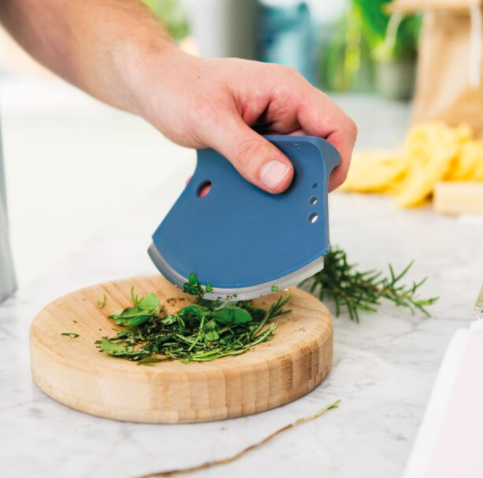 Someone chopping herbs on the circular bamboo tray using the curved chopping tool