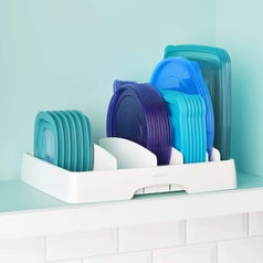 The large white organizer holding different size plastic food storage container lids