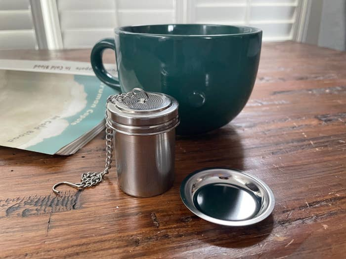 The tea strainer next to its plate and a mug
