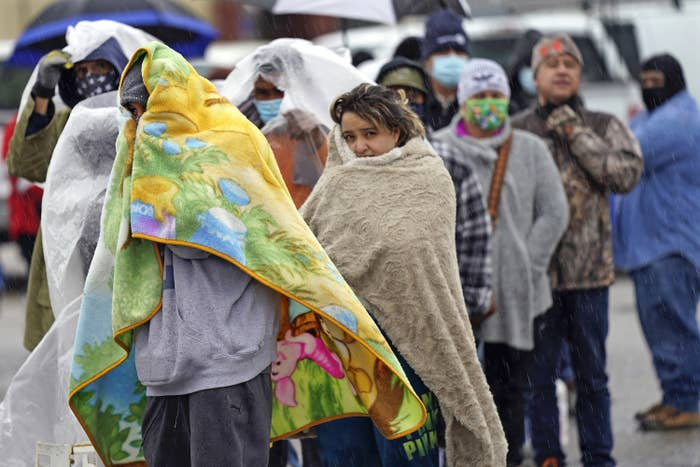 A line of people standing outside wrapped in blankets