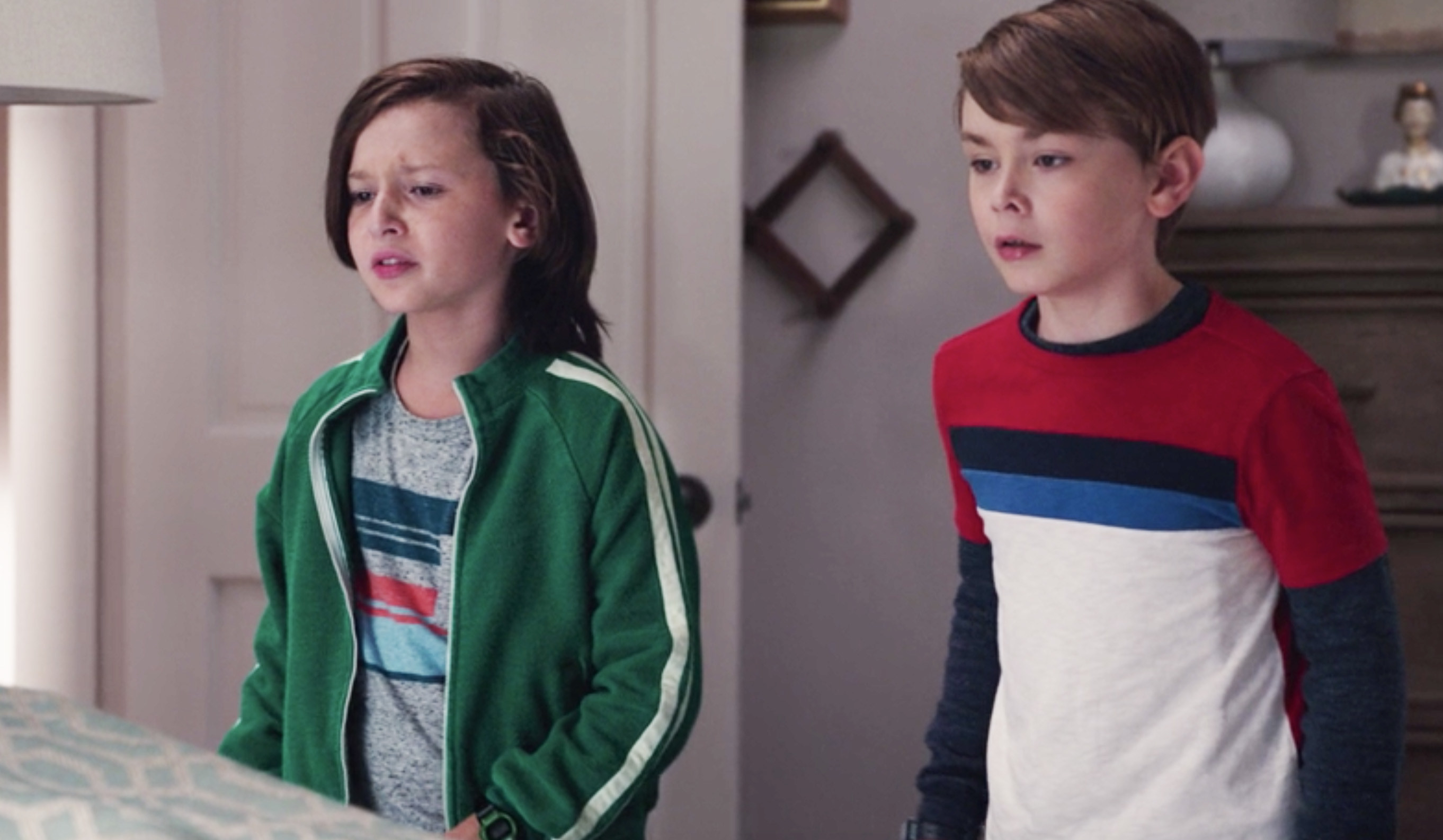 Tommy wearing a green jacket with a white stripe and Billy wearing a red, black, blue, and white striped shirt