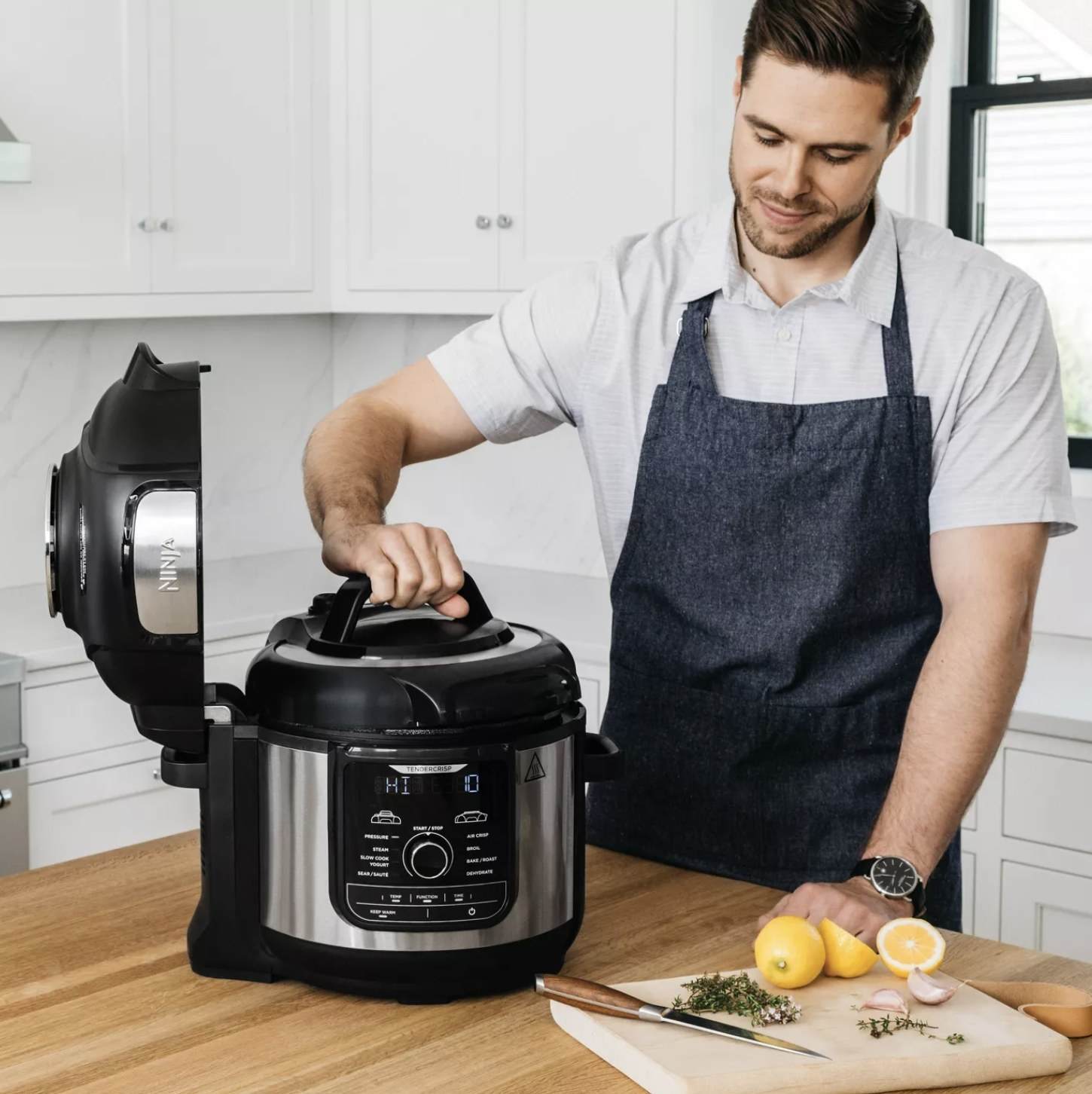 Person is lifting the lid of a Ninja pressure cooker