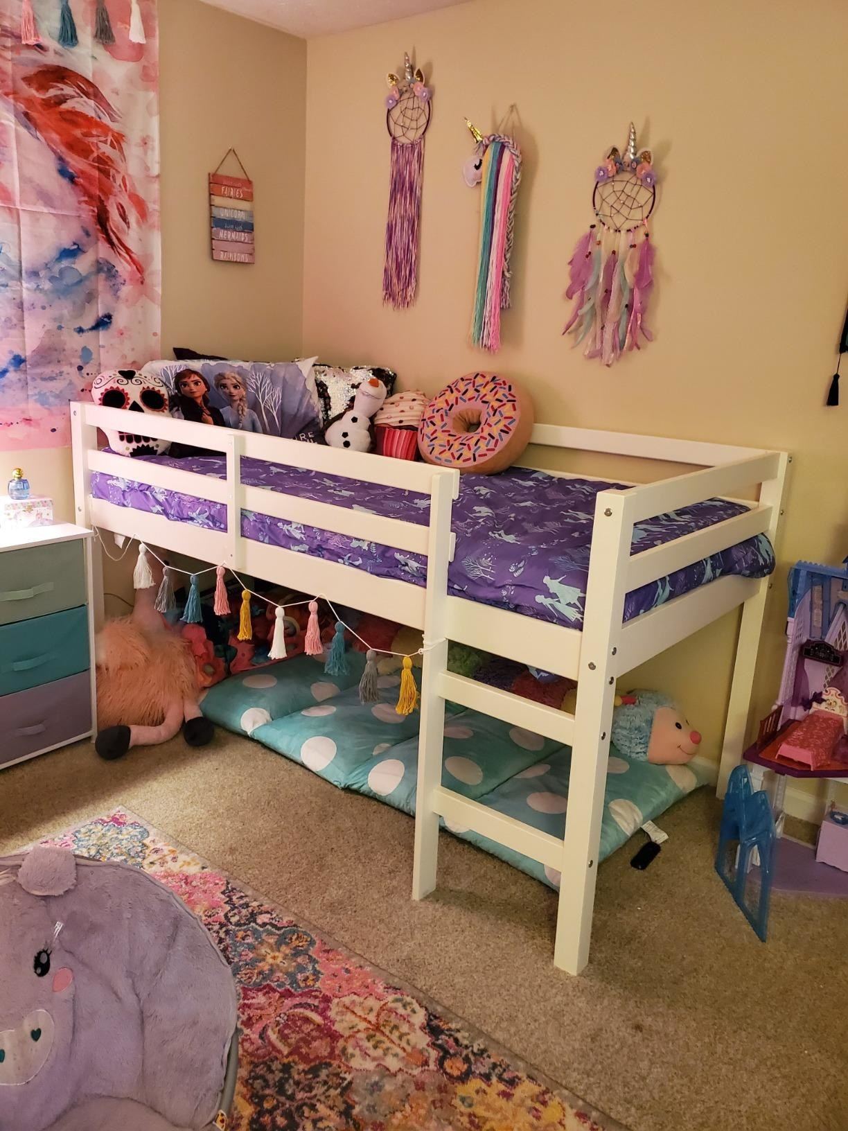 reviewer's photo of the lofted white bed frame with a play space underneath