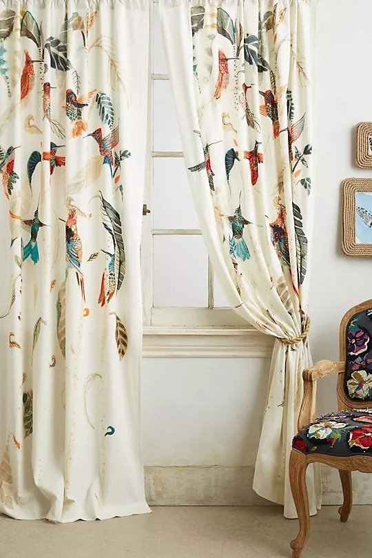 Cream curtains with rope tiebacks and colorful hummingbirds