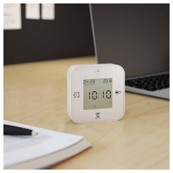A white square-shaped digital device that is a clock, thermometer, and timer.