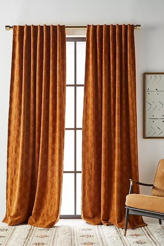 Rust colored curtains with embroidered diamond shapes
