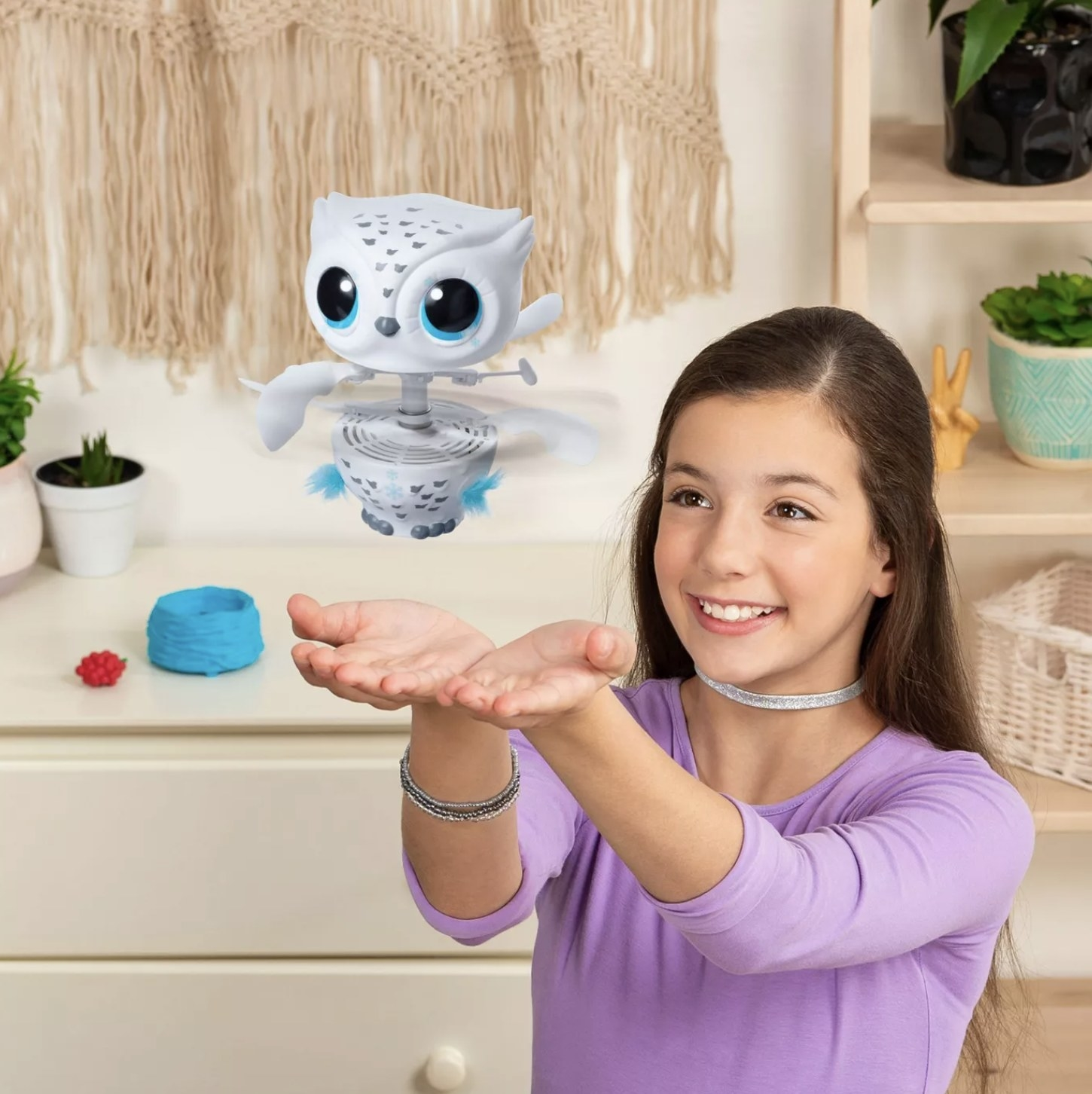 A person playing with an Owleez interactive pet