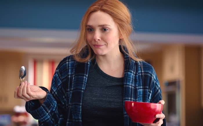 Wanda holding a bowl of cereal, wearing a flannel robe, and looking confused