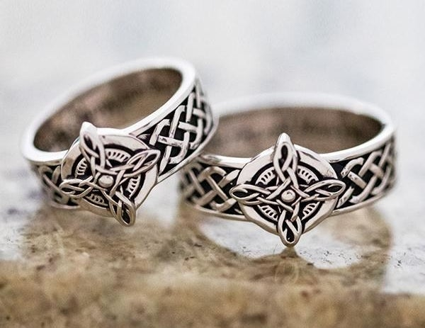 A pair of matching silver rings with an intricate Celctic design on the band and center with interior engraving