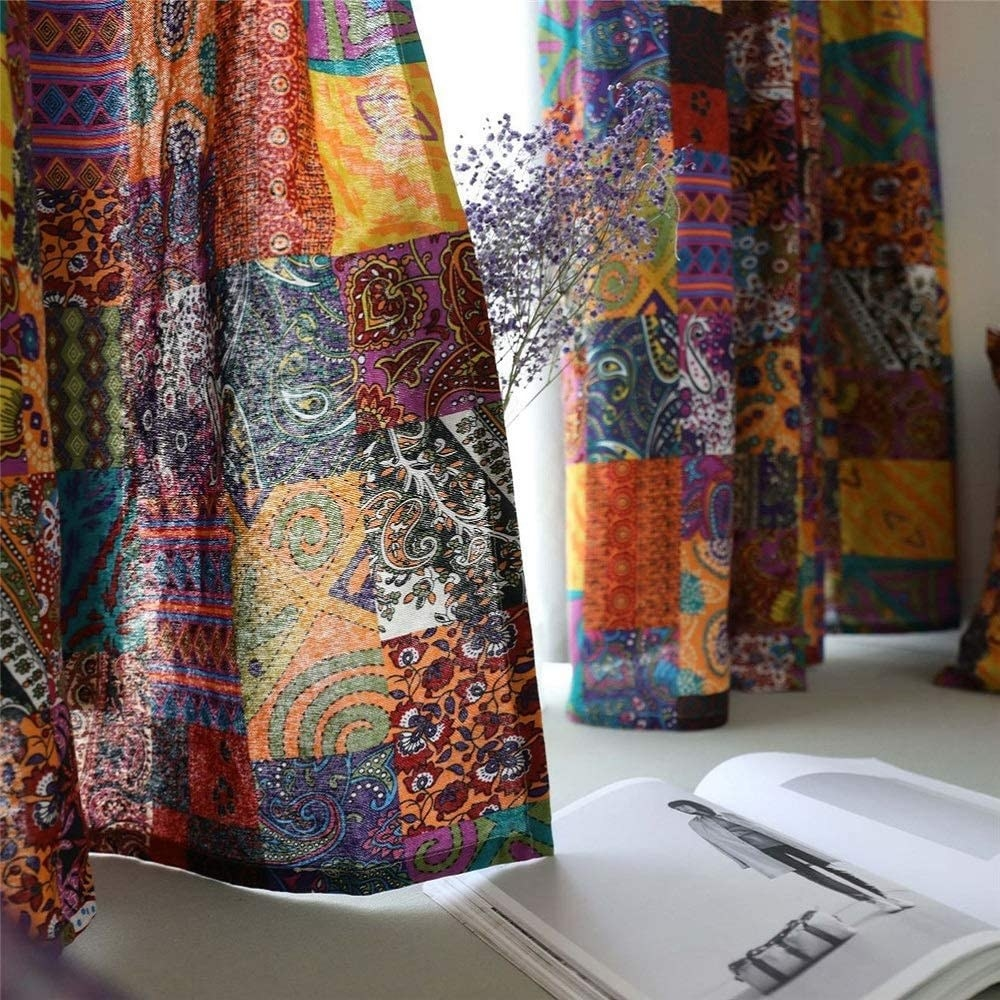 Long curtains with pieced-together squares with different fabrics in several different patterns and colors