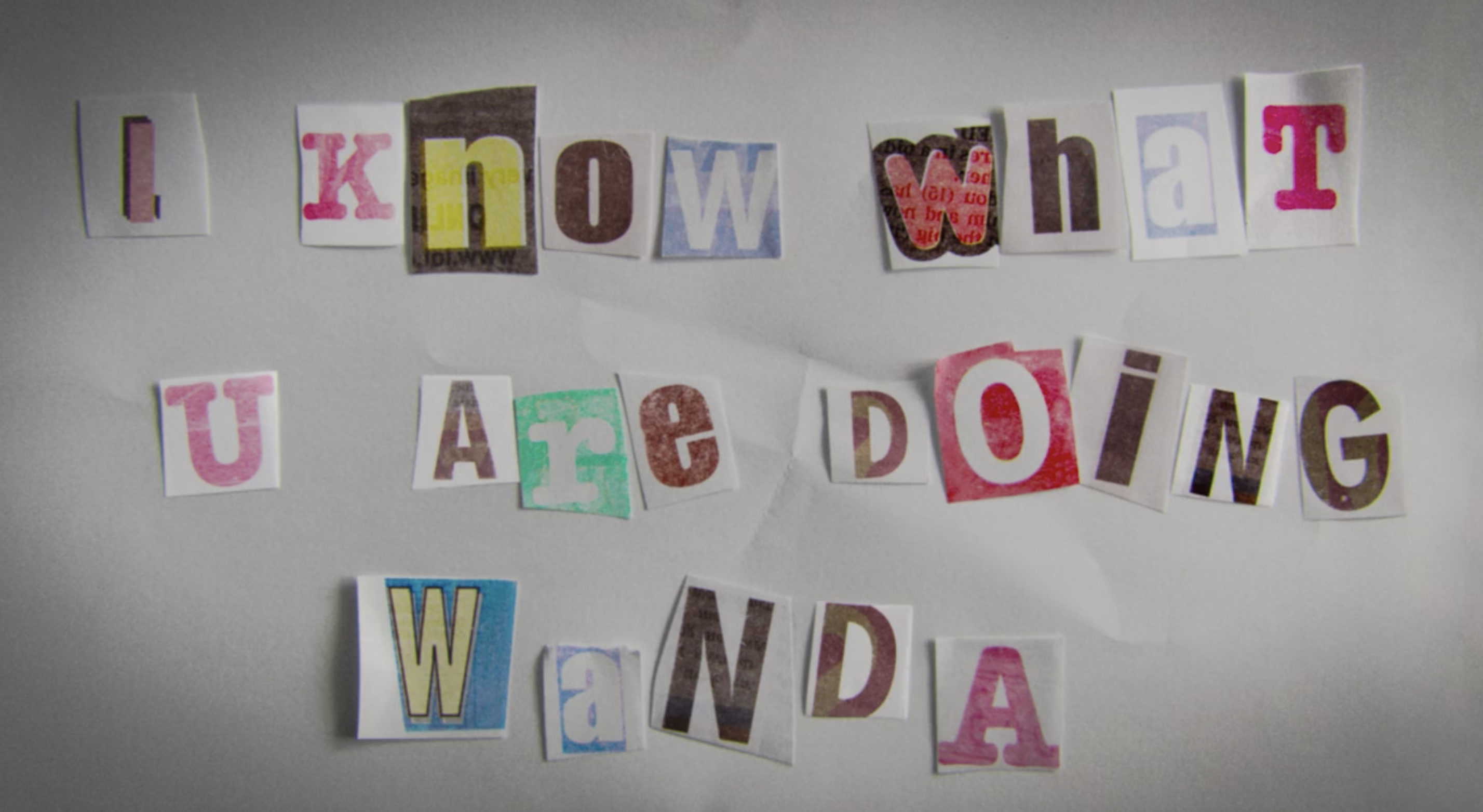 "Cutouts of letters with different fonts that spell out, ""I know what U are doing Wanda"""