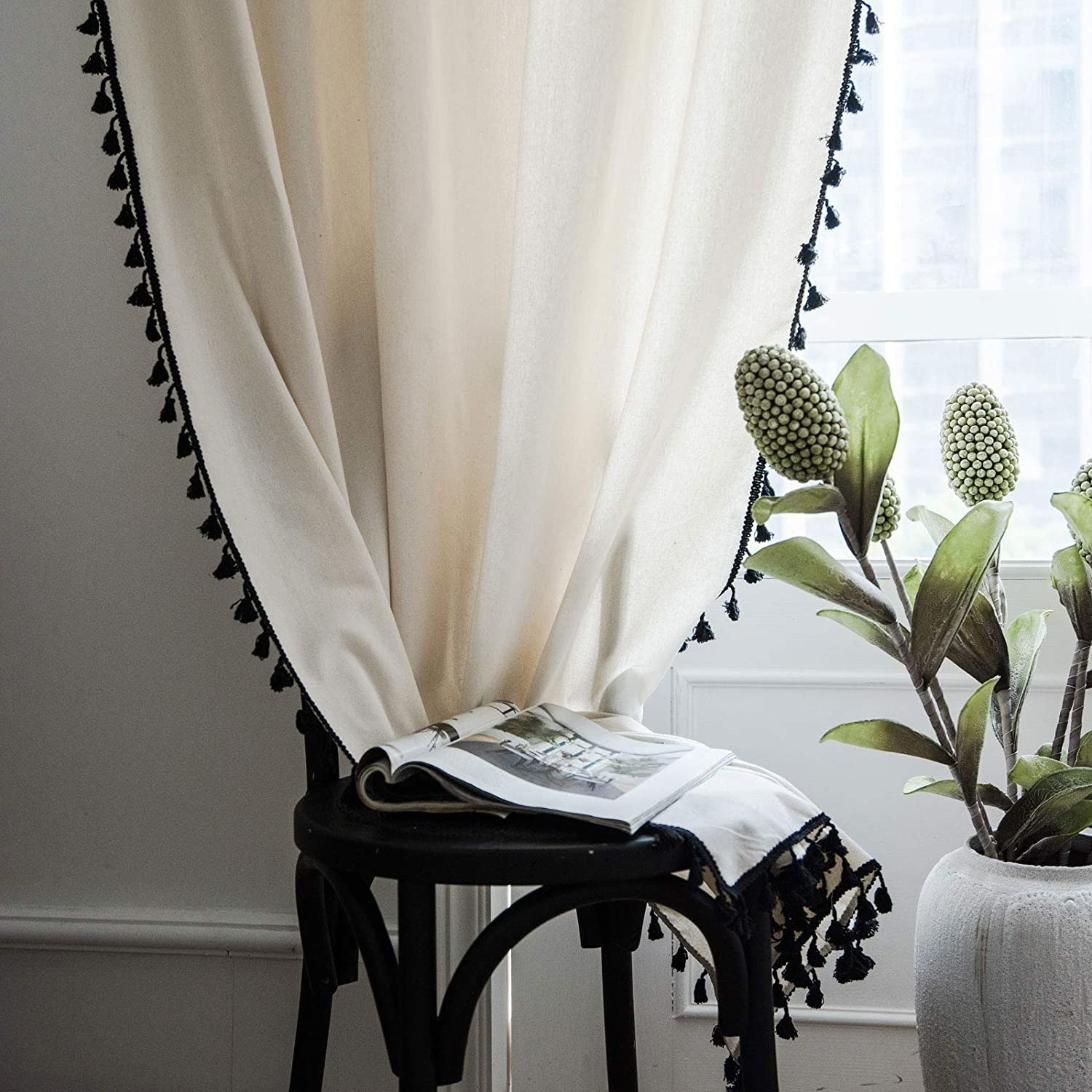 Cream curtain with black tassels on the edges