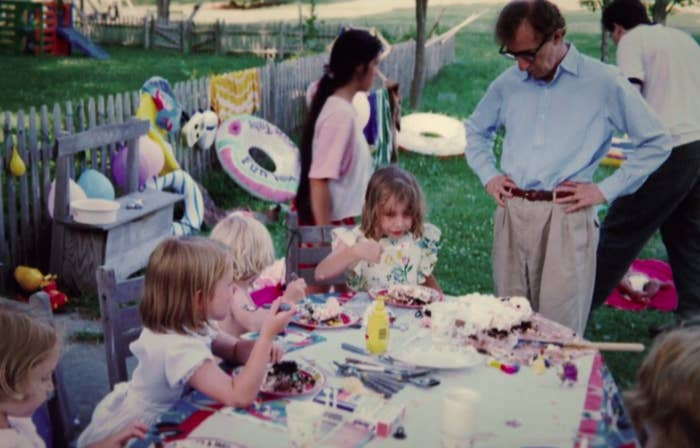 Allen stands over Dylan as she eats cake surrounding by other kids at an outdoor party in an image from the documentary