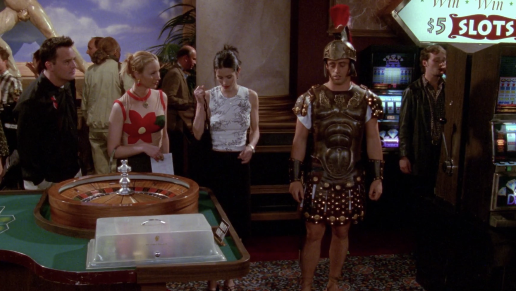 Phoebe, Monica, and Chandler finding Joey at a casino in a Trojan costume