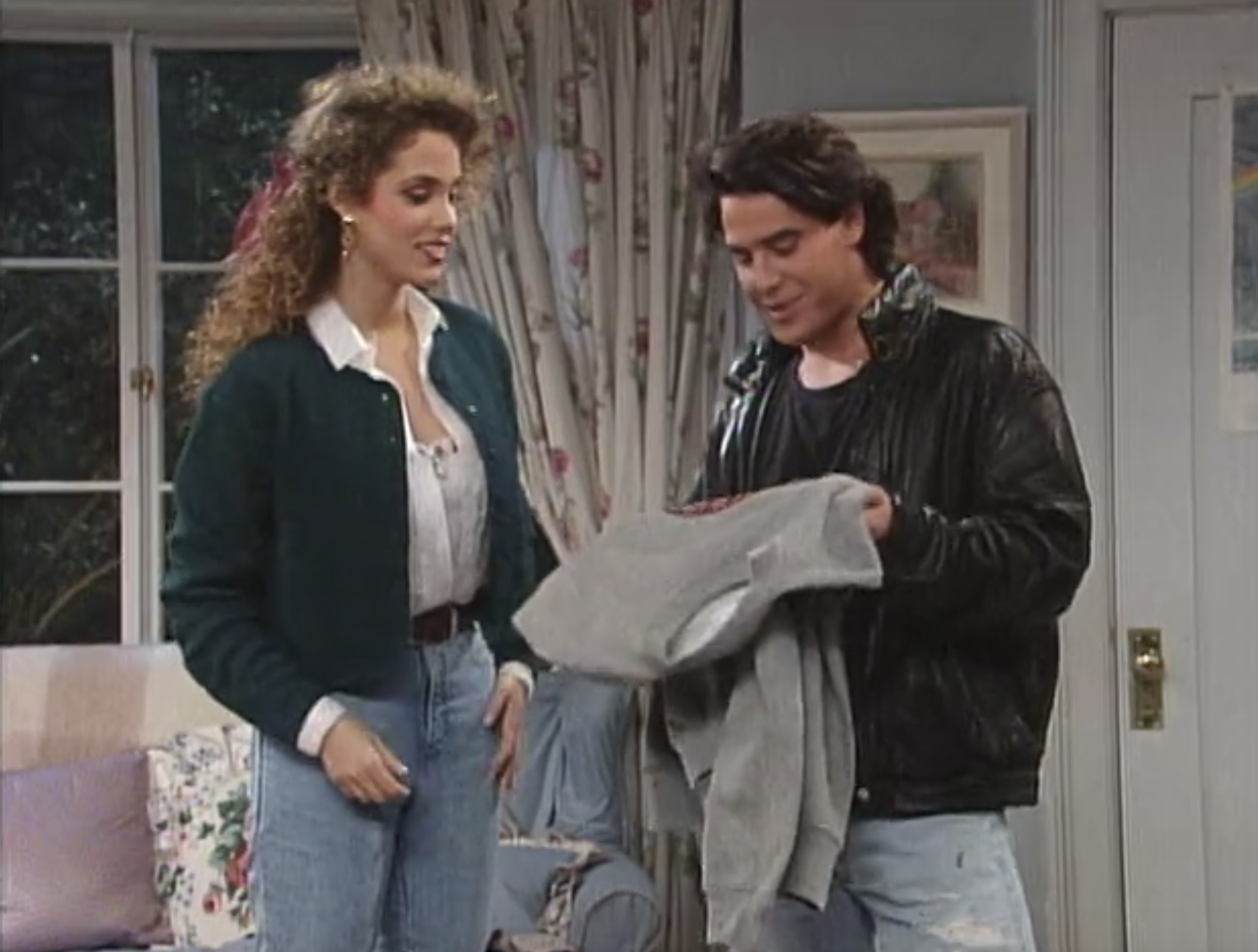 Eric and Jessie talking in a bedroom as he holds a sweater