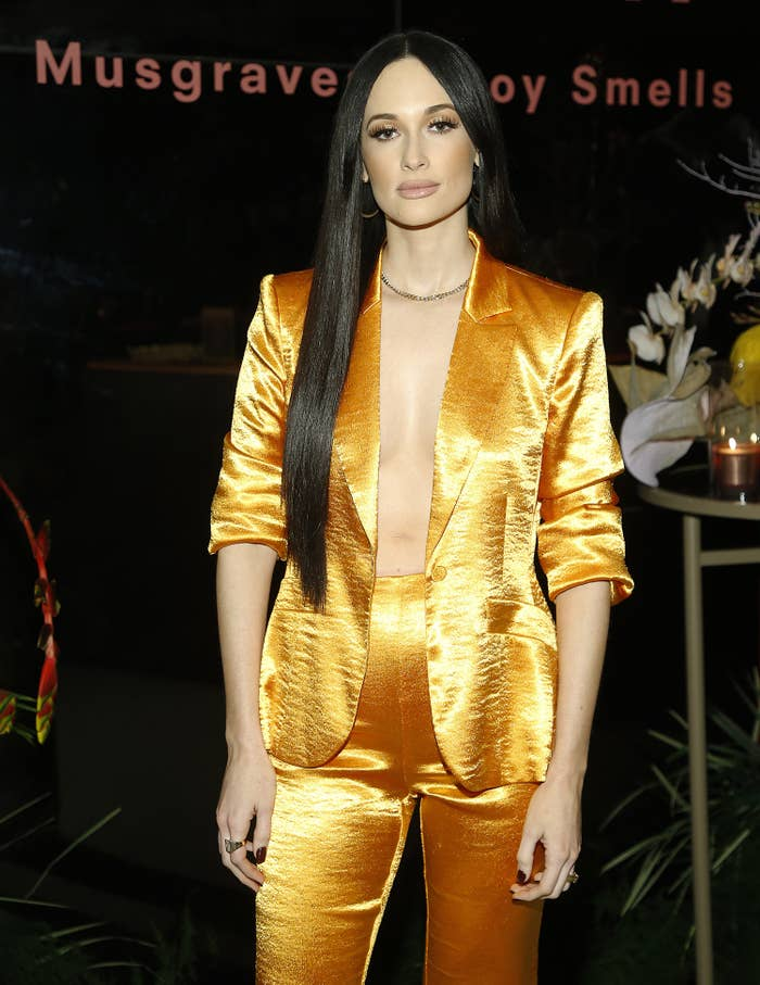 Kacey Musgraves at the launch of her Slow Burn candle in New York City wearing a metallic suit with her jacket completely unbuttoned and no shirt underneath