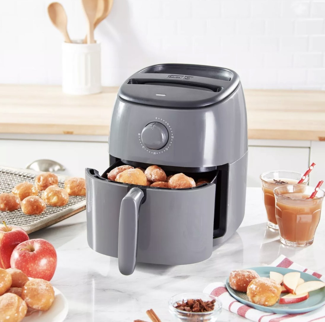 the air fryer in dark gray with donuts in it