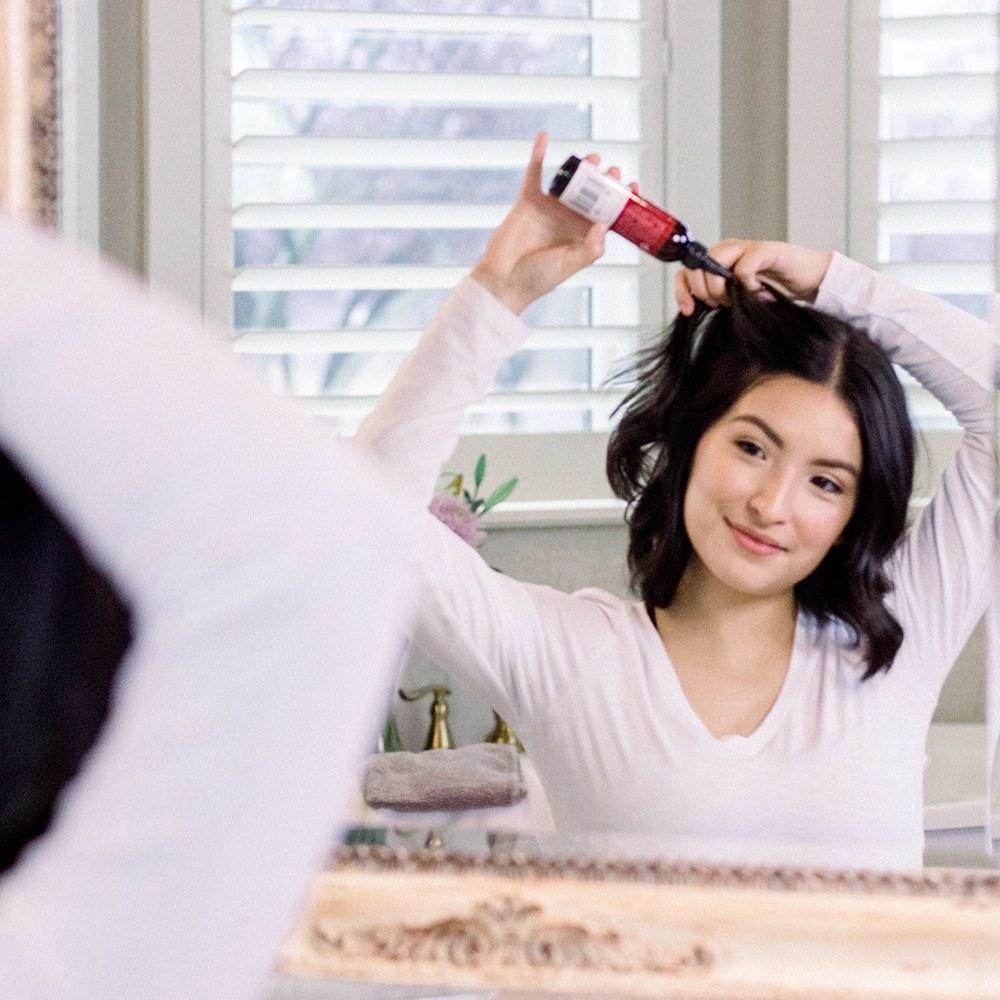 Model applying dry shampoo powder to hair