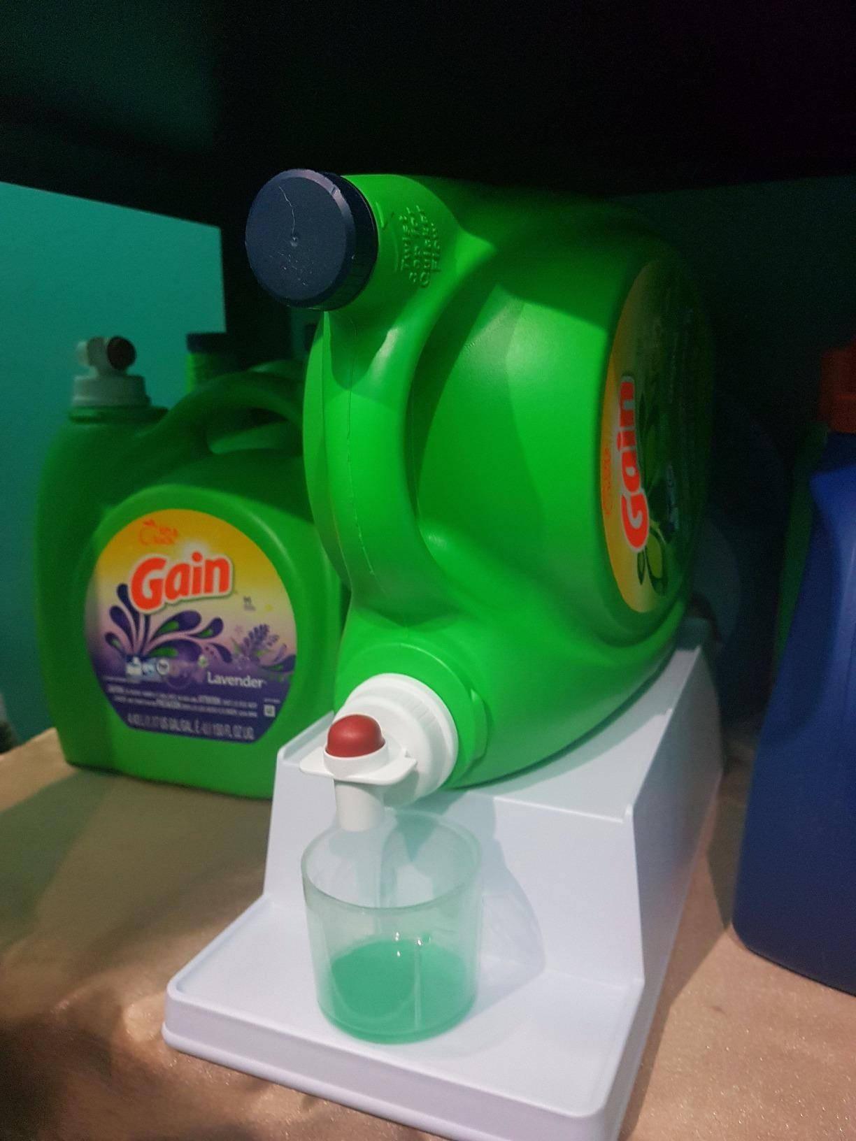 the two-tier white stand holding a sideways detergent bottle on top and a detergent cup below, so the bottle can pour right into it
