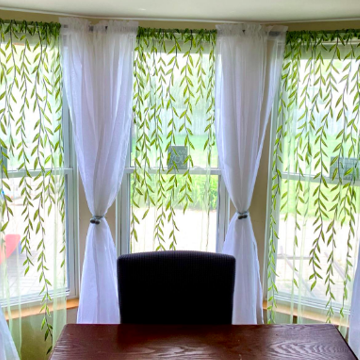 Dining room with sheer drapes over three large windows that look like vines hanging down