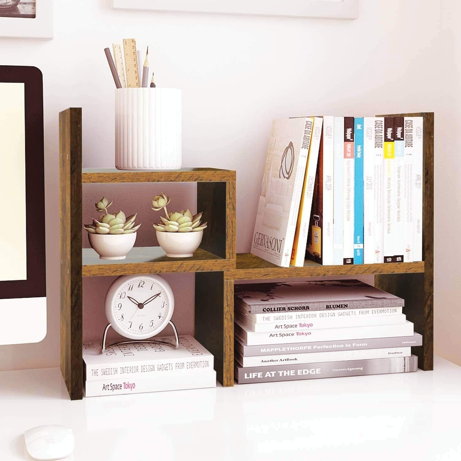 wooden shelf set holding plants, books, a clock, and a pencil cup