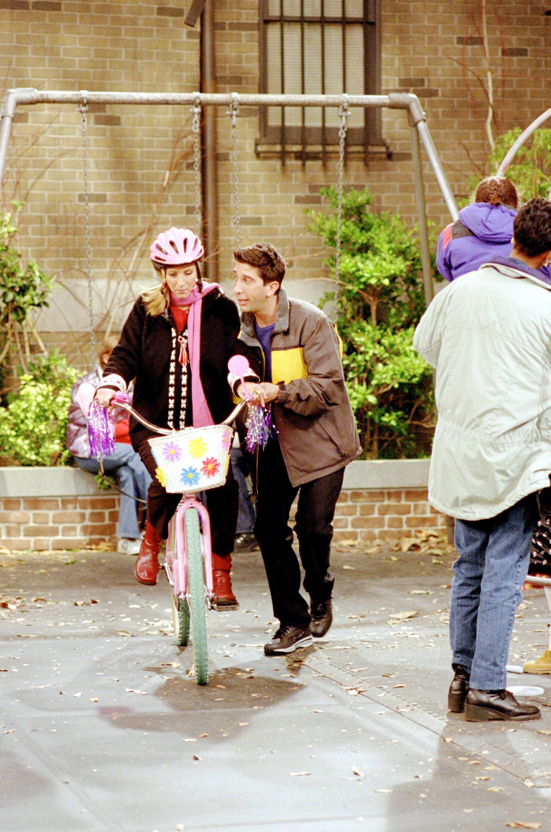 Ross helping Phoebe learn to rid e abike