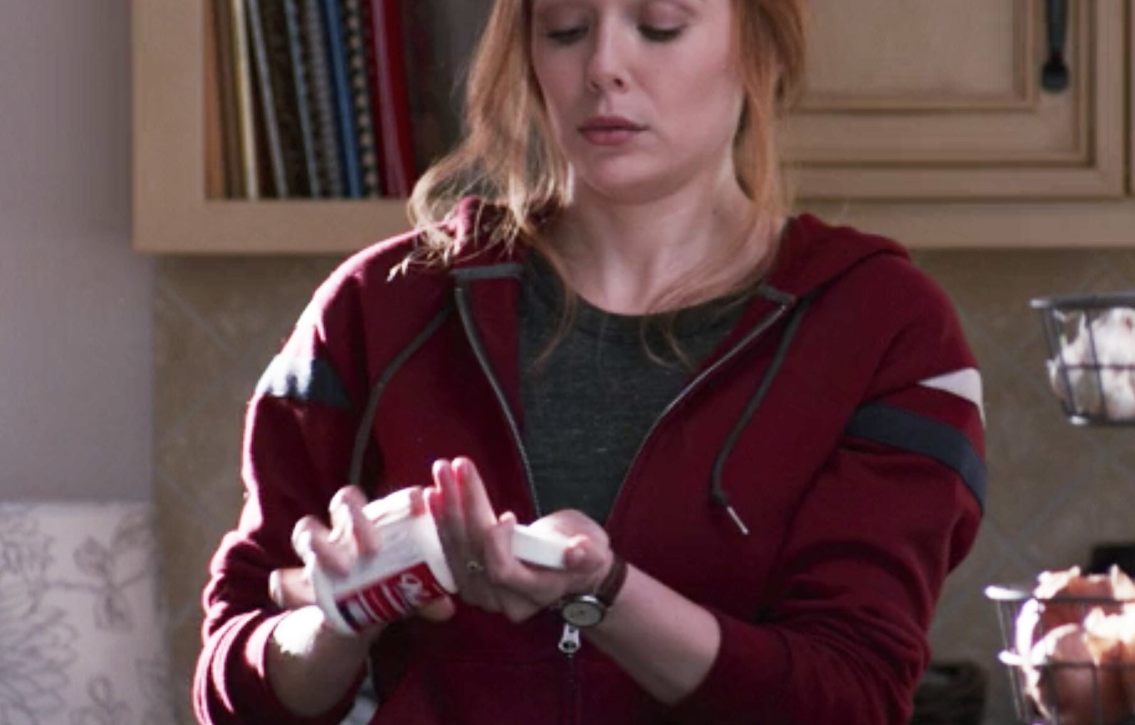 Wanda pouring a pill from a bottle into her hand