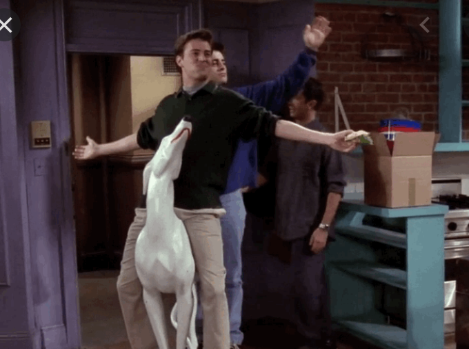 Joey and Chandler wheeling into Monica and Rachel's apartment on the dog statue