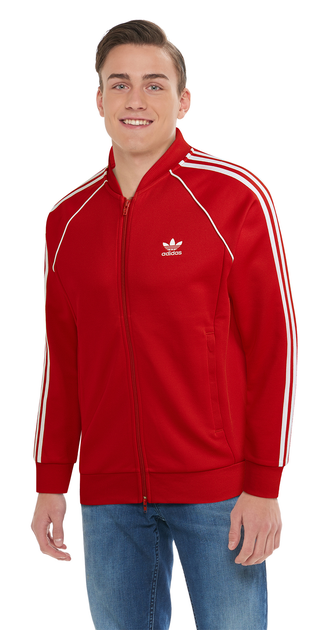 model in red Adidas track jacket and jeans