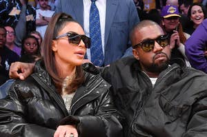 Kim Kardashian and Kanye West sit courtside at a basketball arena, each wearing fashionable outfits and sunglasses
