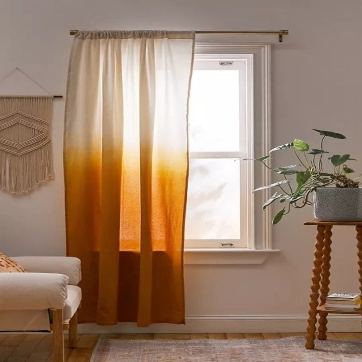 Long ombre curtain panel with rusty orange at the bottom fading into cream at the top