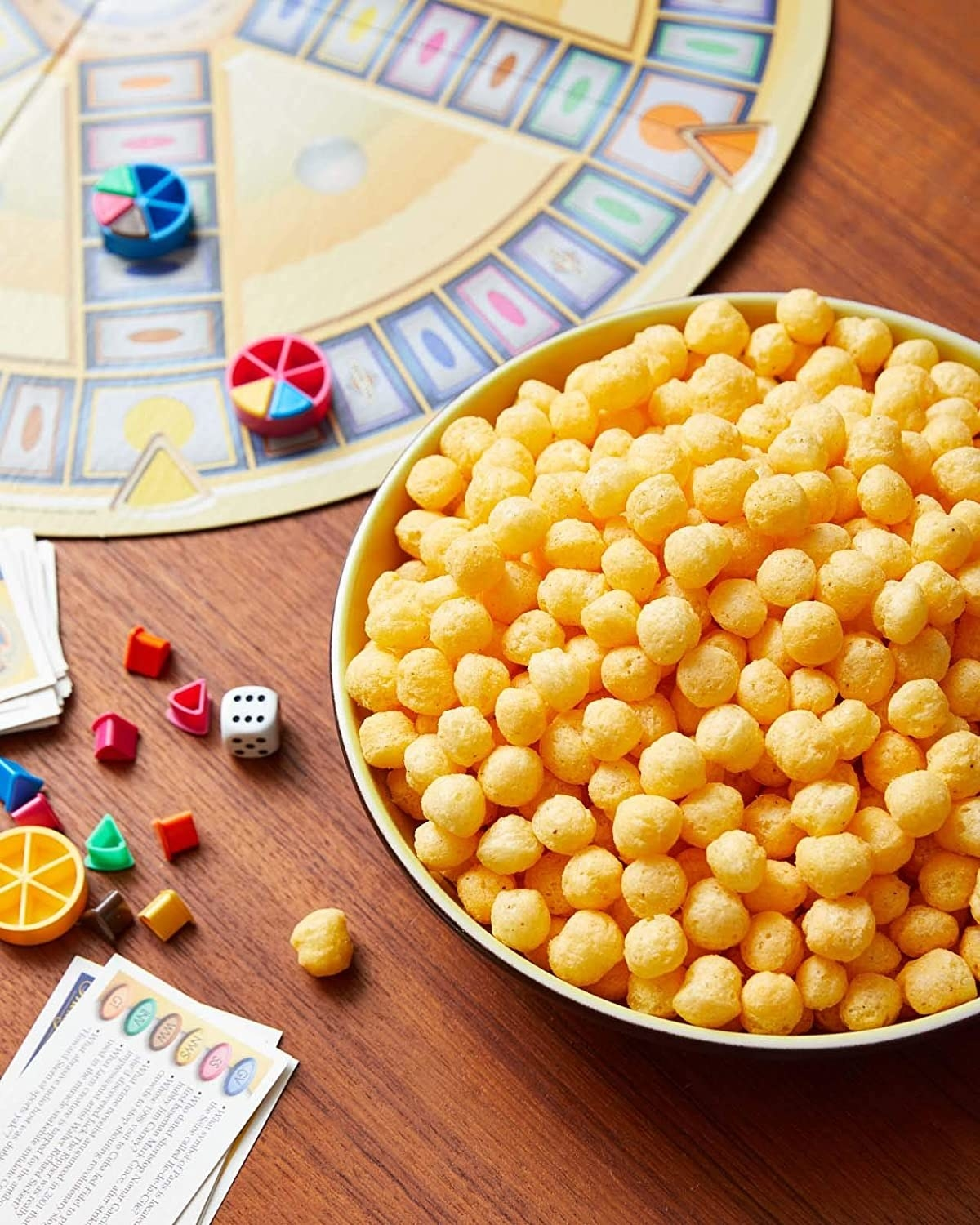 bowl of the cheeseballs beside a board game
