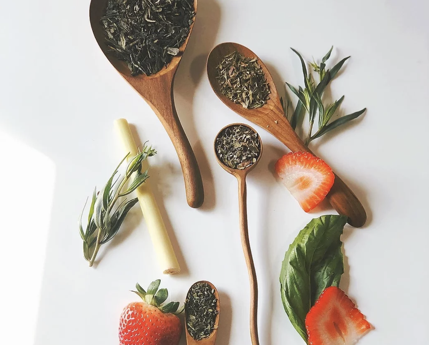 wooden spoons holding the loose leaf tea with strawberries surrounding them