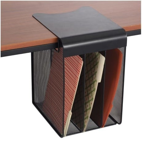 the black mesh wire organizer hanging off a table and holding a file folder in each compartment